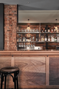 A Bar, with a palette of recycled timber, black steel and honed stone